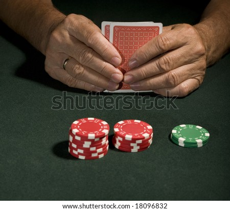 Casino chips on a green background and poker player in Vegas holding cards