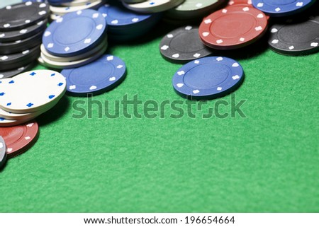 casino chips on a green felt - stock photo