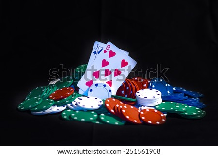 Casino chips, playing cards isolated on black background - stock photo