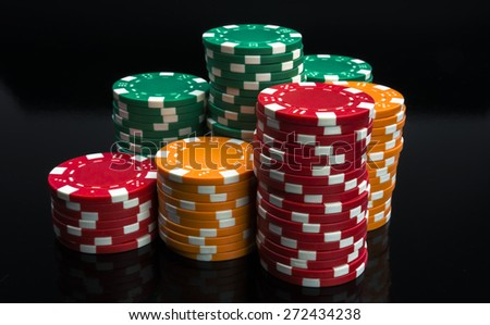 Casino chips stacks on black background. - stock photo