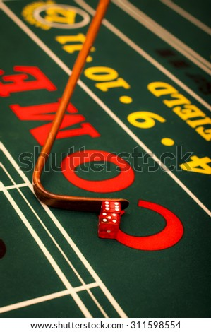 Casino dealer pushing a pair of dice on a craps table