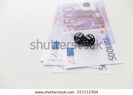 casino, gambling and fortune concept - close up of black dice and euro cash money - stock photo