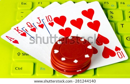 Casino gambling chips and royal straight flush in computer Keyboard green - stock photo