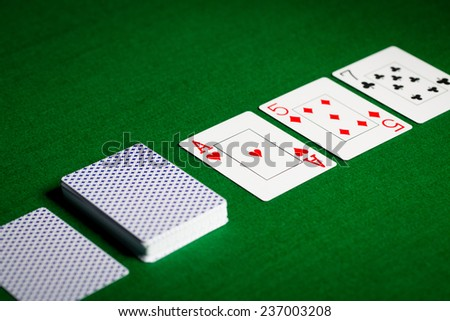 casino, gambling, poker, and entertainment concept - playing cards on green table surface - stock photo