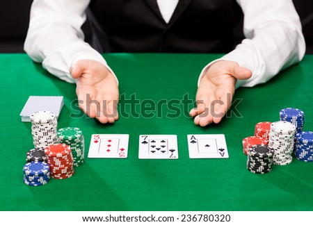 casino, gambling, poker, people and entertainment concept - close up of holdem dealer with playing cards and chips on green table - stock photo