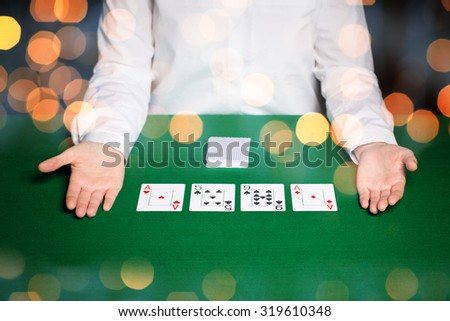 casino, gambling, poker, people and entertainment concept - close up of holdem dealer with playing cards on green table over holidays lights background