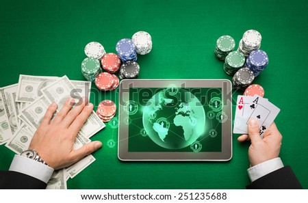 casino, online gambling, technology and people concept - close up of poker player holding playing cards, chips and earth projection with users icons on tablet pc computer screen at green casino table - stock photo
