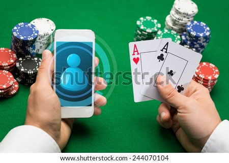 casino, online gambling, technology and people concept - close up of poker player with playing cards, smartphone and chips at green casino table - stock photo