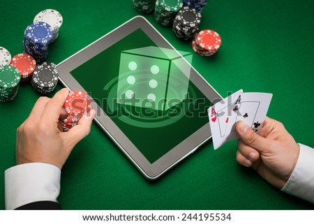 casino, online gambling, technology and people concept - close up of poker player with playing cards, tablet pc computer and chips at green casino table - stock photo