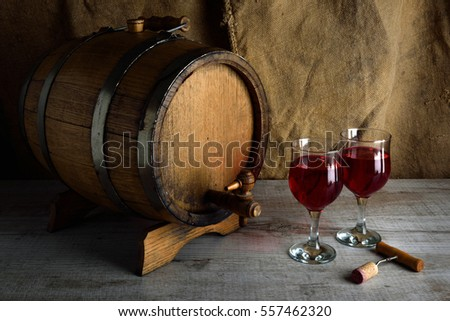cask of wine on a wooden background with a glass of wine and bottle of  wine