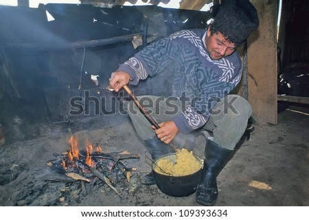 CASOLT, ROMANIA - SEPTEMBER 28: Unidentified shepherd cooks mamaliga on September 28, 1997 in Casolt, Romania. Those shepherds represents traditional culture in Romania.