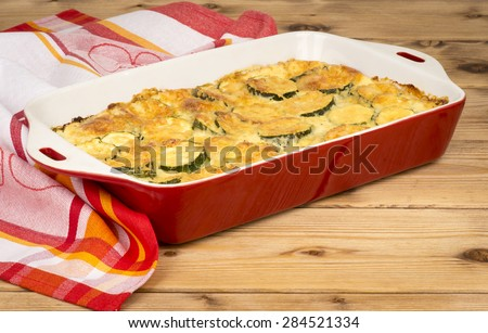 Casserole with cheese and zucchini in baking dish on the wooden background. - stock photo