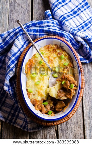Casserole with potatoes and mushrooms in a rustic style on the wooden background. Selective focus.