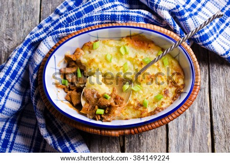Casserole with potatoes and mushrooms in a rustic style on the wooden background. Selective focus. - stock photo
