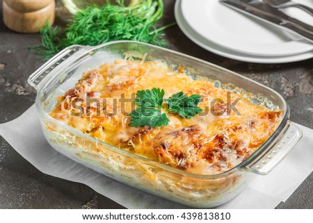 Casserole with potatoes, melted cheese, fresh green apple and lemon - stock photo