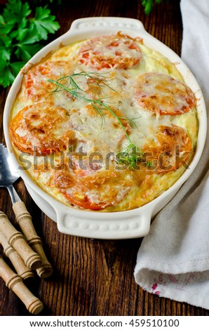 Casserole with rice, sea bass, tomato and cheese - stock photo