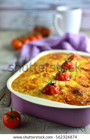 Casserole with tomatoes on a gray table dinner