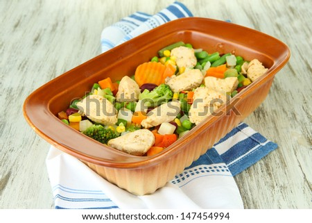Casserole with vegetables and meat, on wooden background - stock photo