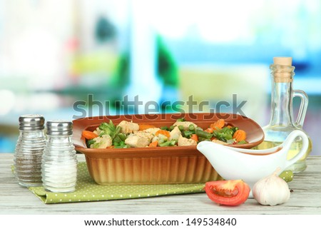 Casserole with vegetables and meat, on wooden table, on bright background - stock photo