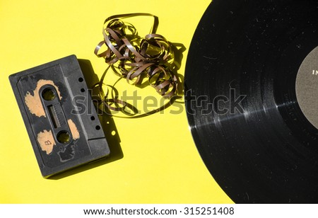 cassette and vinyl record on a colored background yellow retro - stock photo