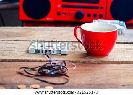 Cassette tape over and coffee cup on wooden table vintage effect - stock photo