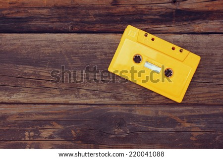 Cassette tape over wooden table. top view. image is retro filtered. room for text - stock photo