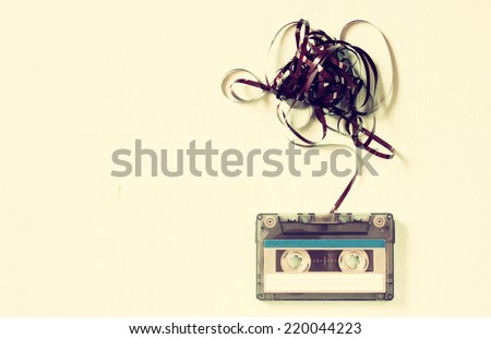 Cassette tape over wooden table with tangled ribbon. top view.  retro filter