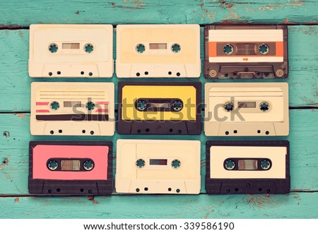Cassette tapes over blue textured wooden table . top view. retro filter - stock photo