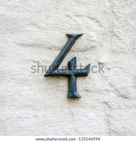 cast bronze house number four on a white plastered wall - stock photo