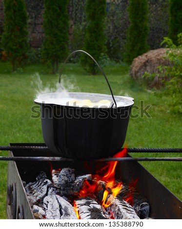 Cast iron cauldron over an open fire. Cooking. - stock photo