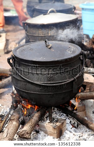 Cast Iron cooking pots on wood fire. Traditional zulu cooking pot