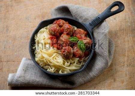 Cast-iron frying pan with tagliatelle and meatballs, studio shot - stock photo