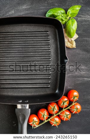 Cast iron griddle pan on black background with vegetables - stock photo