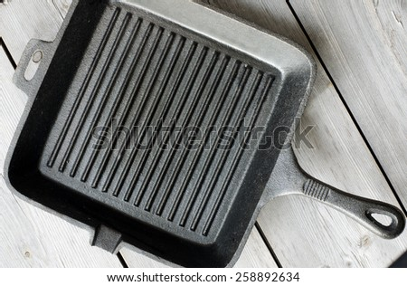 Cast iron griddle pan on wooden background - stock photo