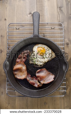 cast iron pan with grilled bacon and fried egg with chive - stock photo