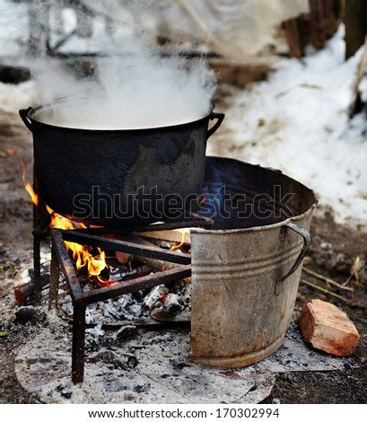Cast iron pot boiling water outdoor in a rural area
