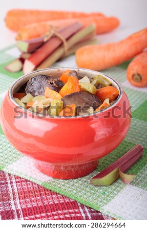 Cast iron pot with baked chicken liver, carrots and rhubarb - stock photo