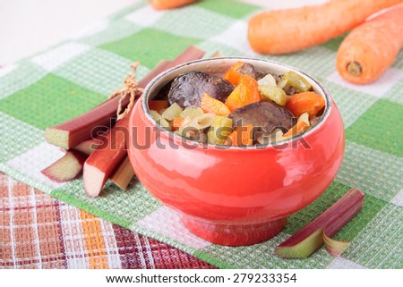 Cast iron pot with chicken liver, carrots and rhubarb - stock photo