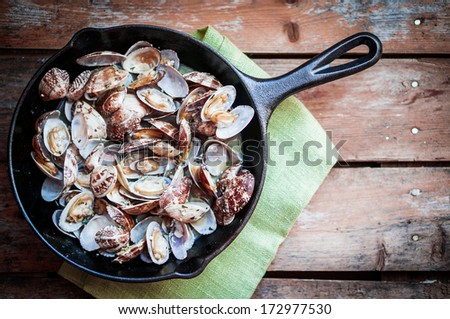 Cast iron skillet of Delicious Fresh Steamer Clams with Garlic on rustic wooden background - stock photo