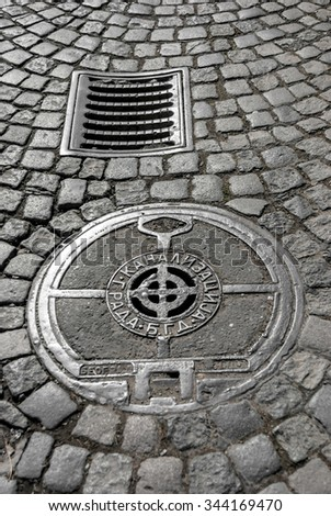 "Cast iron storm drain and sewer manhole cover on cobblestone street. Content cyrillic caption: ""City Sewage B.G.D."". (""B.G.D."" is stands for Belgrade, Serbia) - stock photo"