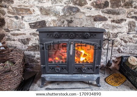 Cast iron stove burning wood logs against a robust stone wall - stock photo