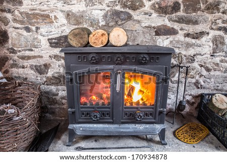 Cast iron wood stove burning logs against a robust stone wall - stock photo