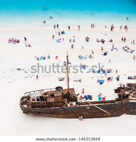 castaways enjoying sunbathing on white sand beach near shipwreck - stock photo