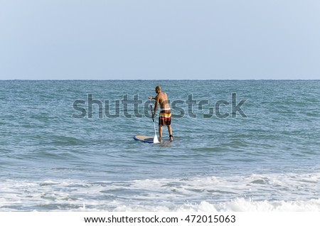 CASTELLON, SPAIN - AUGUST 1th 2016: Stand up paddle surfing. Surfer over his surfboard, in the beach of Castellon de la Plana, on August 1th 2016.