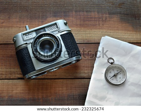 Castellon,Spain.November 21,2014.Old style reflex camera and compass with old paper sheet on a wooden surface - stock photo