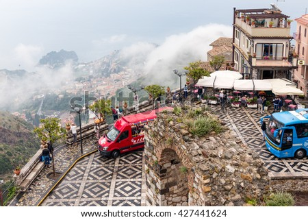 CASTELMOLA, ITALY - MAY 19: Panorama of Castelmola town square with tourists buses and an aerial view at Taormina covered with raining clouds on May 19, 2016 in Castelmola at the island Sicily, Italy