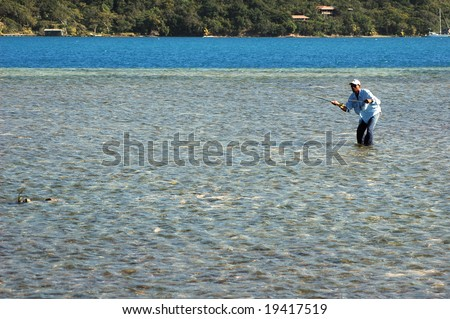 Casting for bonefish on the Honduran Island of Roatan. Here is a guide casting towards a shoal of bonefish using a sidecast to reduce the overall profile to avoid spooking the fish. - stock photo