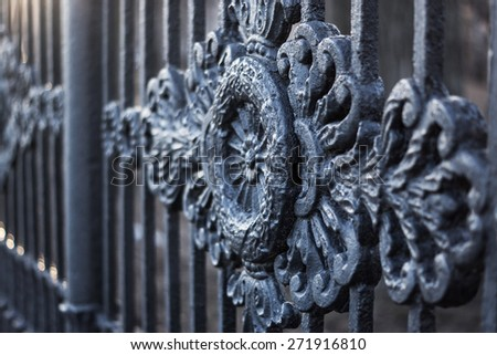 Casting ornament on a wrought cast iron fence in a park - stock photo