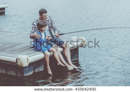 Casting that fish off. Top view of father and son fishing together on quayside - stock photo