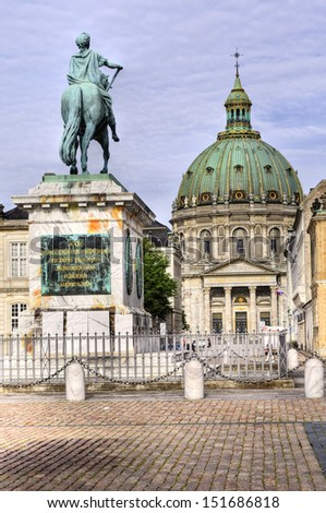 Castle Amalienborg with statue of Frederick V in Copenhagen, Denmark. The castle is the winter home of the Danish royal family - stock photo